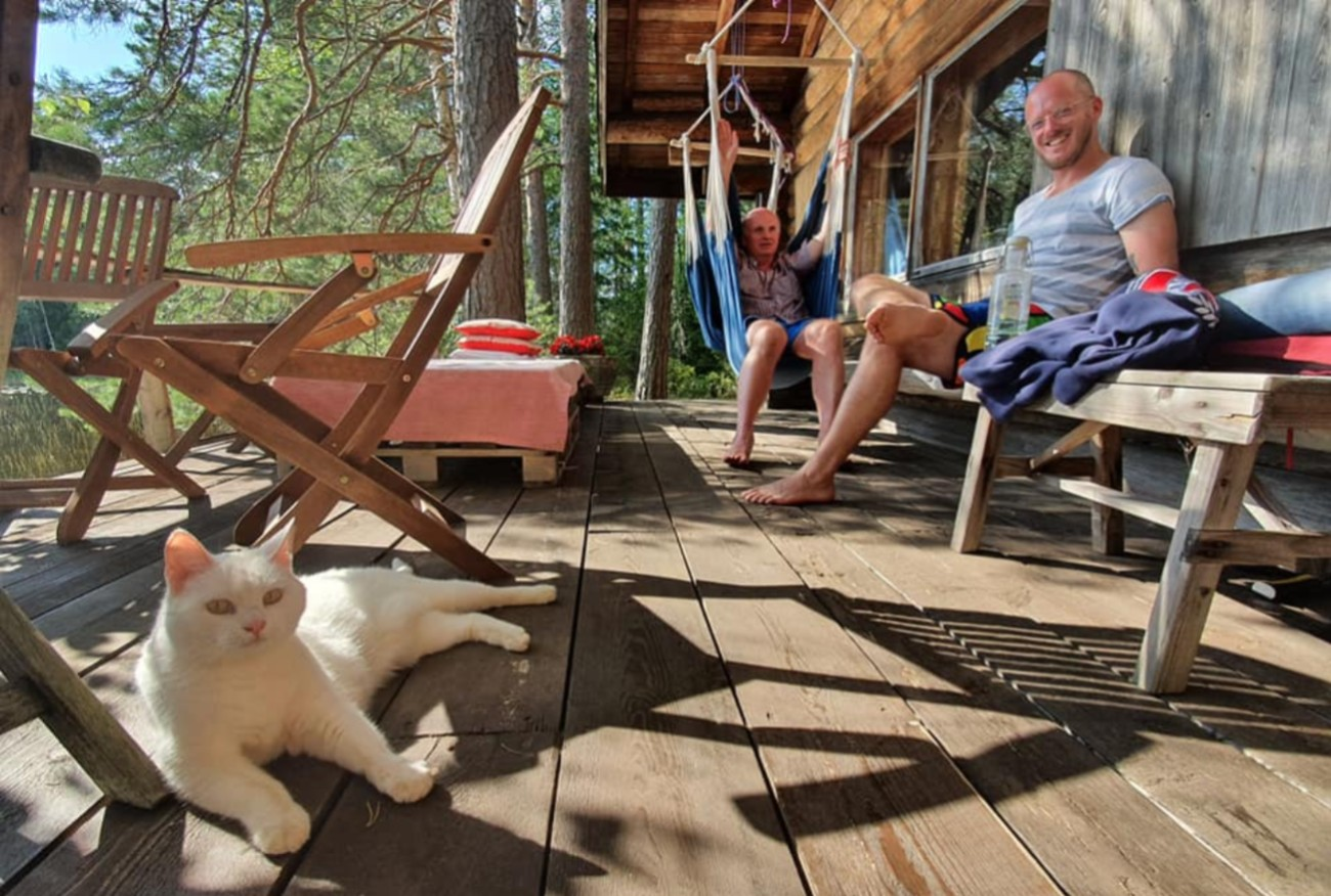 Pete And Bernie Of Honesty Europe Sitting On Porch At The Cabin In Finland With Cat