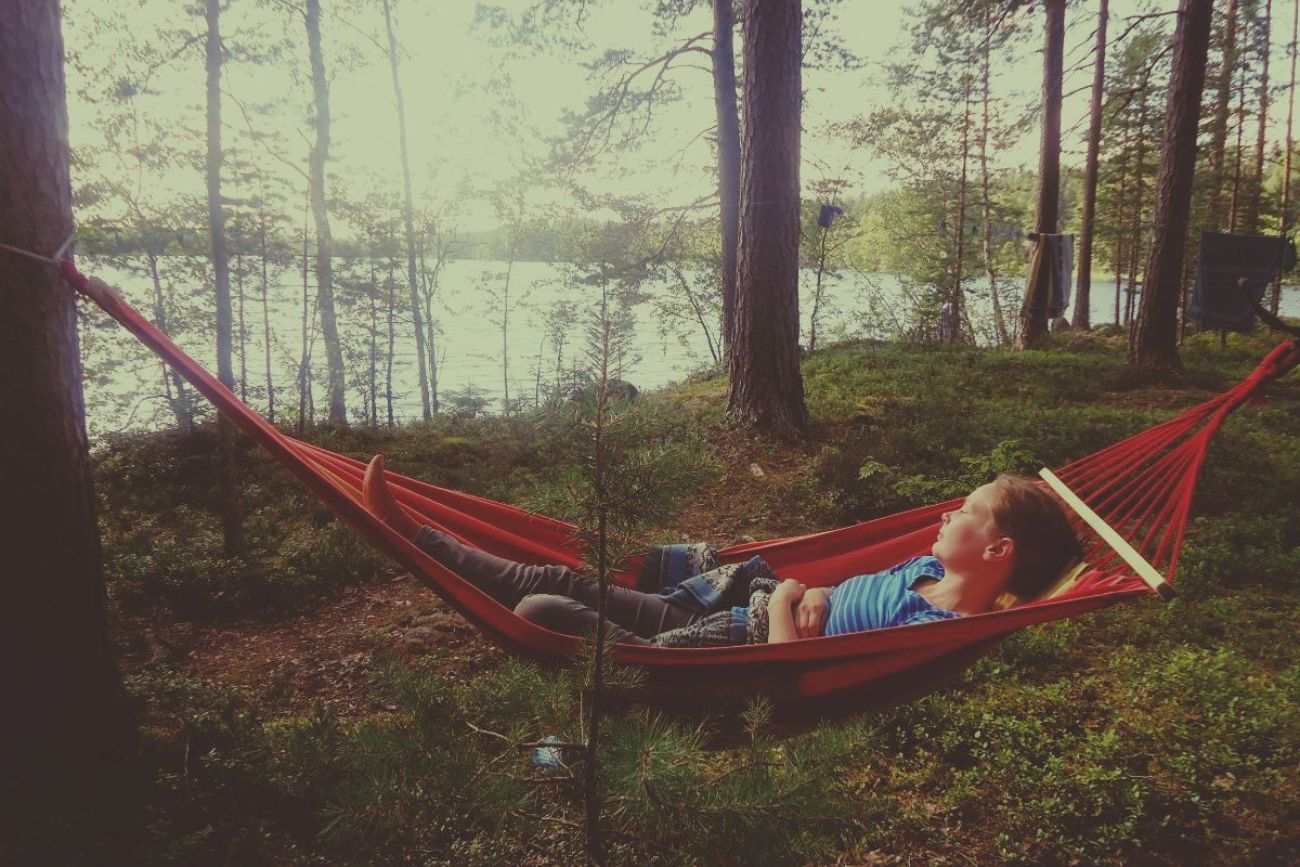 Woman Lying In Red Hammock In The Forest Near Lake In Finland