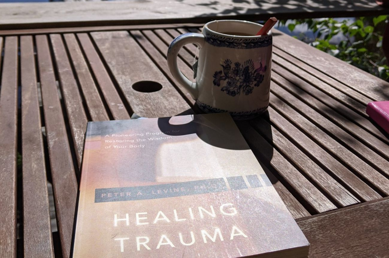 Peter Levine's Healing Trauma Book On Table With Coffee Mug