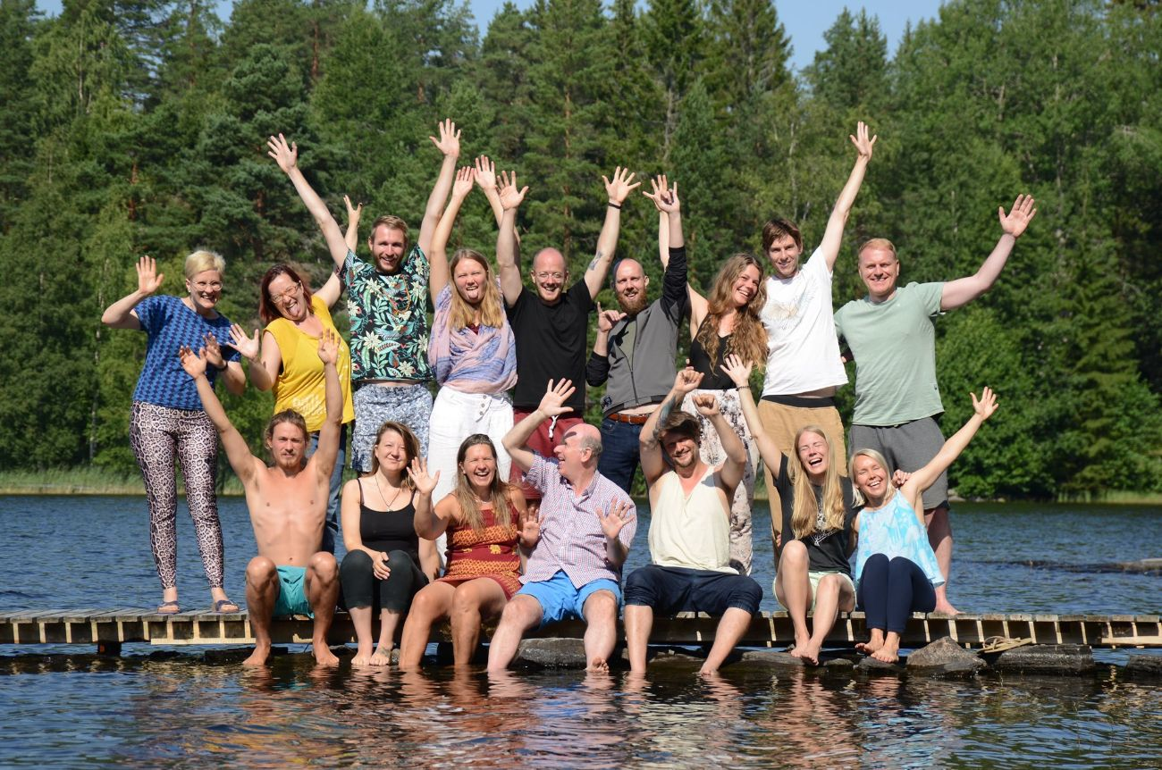 Honesty Europe Community Gathering In Orivesi, Finland - People Smiling And Saving Hands On A Dock On A Lake