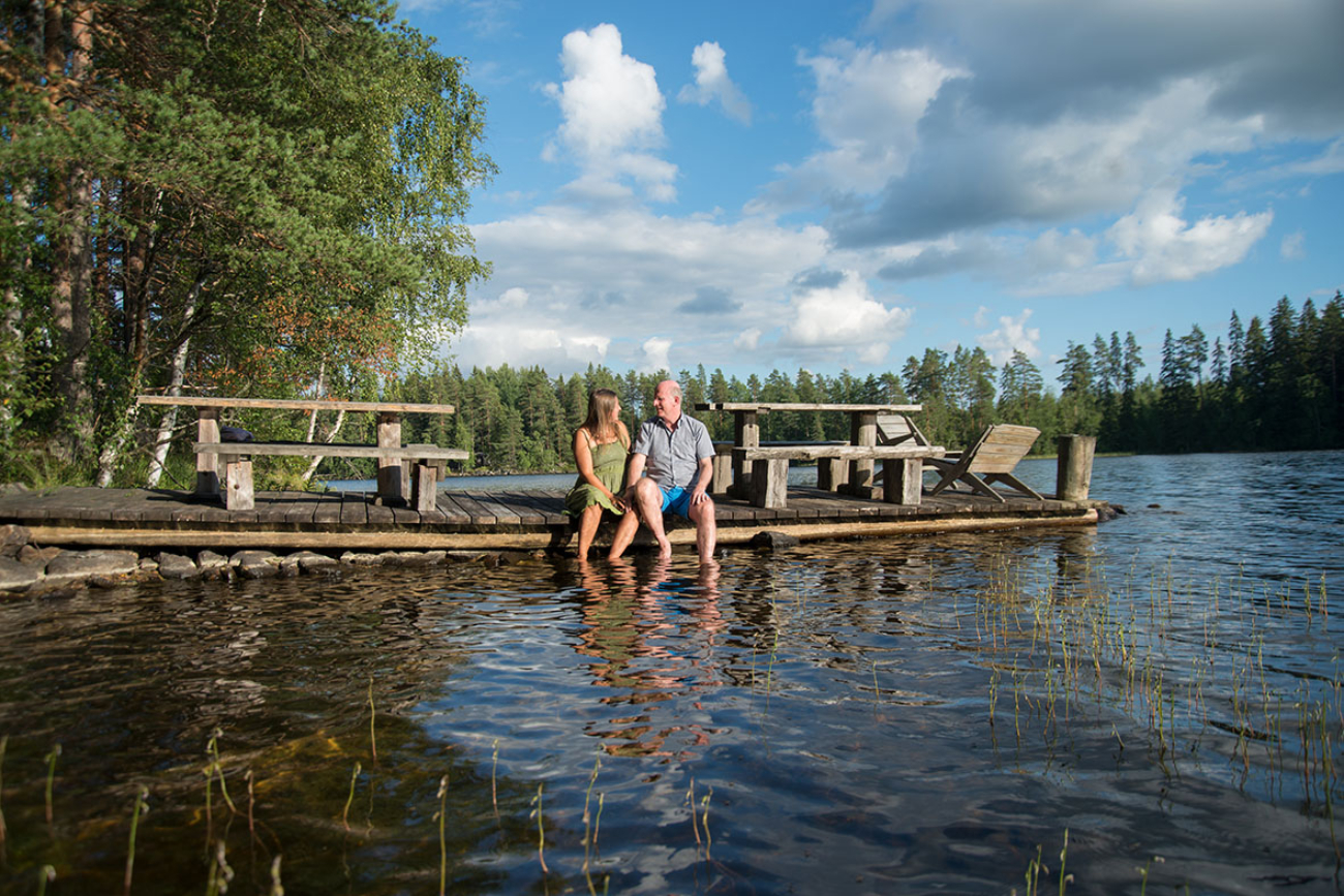 Pete And Tuulia Of Honesty Europe Sitting On The Dock Of The Lake In Finland