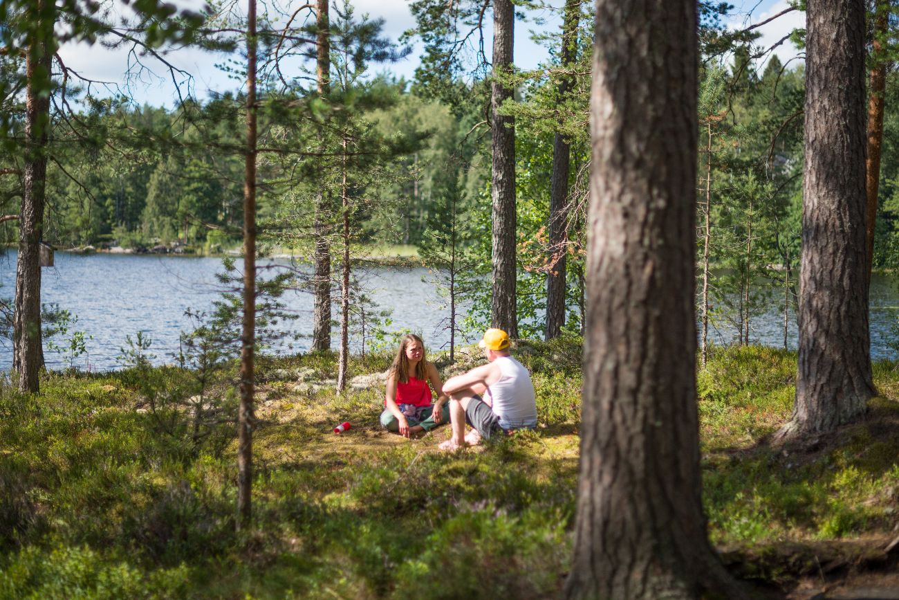 Man And Woman Sitting In Finnish Forest By The Lake